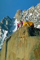 Two climbers setting up a winter camp on a rock peak below Basin Mountain, Eastern Sierra, California.
