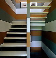 The khaki, grey and white striped stairwell is lined with period photographs of Venice