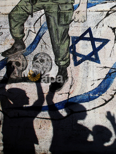 Palestinian children's shadows on a wall with a mural depicting a Palestinian fight and an Israeli flag in the Jabaliya Refugee Camp in northern Gaza Strip on 22 August 2011 Reports state that Palestinian militants fired two missiles at southern Israel on 22 August 2011, despite an announcement earlier in the day that they would stop launching rockets at the Jewish state, the Israeli military said. The rockets landed in open territory near the city of Ashkelon, about 14 kilometres north of the salient. There were no reports of injuries or damage to buildings, but they did set a field alight. Photo by Ali Jadallah
