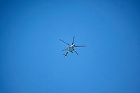 A Syrian army helicopter flies the sky as it shoots the rebel positions in Aleppo City.