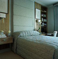 Built-in bedside units flank the bed which has a quilted silk headboard that covers the height of the wall