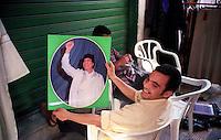 Libyan Arab Jamahiriya   .Tripoli       June 2002. The Medina  Souk Al-Turk .A man shows the portrait of Colonel Muammar Gaddafi.Libia Tripoli  Giugno 2002.La Medina,   Souk Al-Turk .Un uomo mostra il ritratto del Colonnello Muammar Gheddafi.