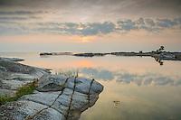 Spegelblank skymning vid en klippa på Kallskär vid havet i Stockholms ytterskärgård.