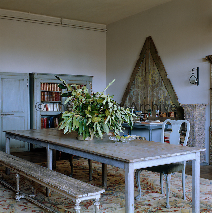 A triangular wooden panel from a Mongolian barn is propped up against one wall of the library/dining room which has a long refectory table in the centre of the room