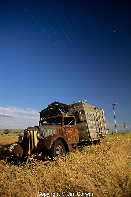 Old dilapidated truck in field near Shaniko ghost town with moon and telephone poles Central Oregon State USA
