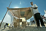 A man fastens together a temporary shelter for his family in a spontaneous camp for quake survivors being established in Croix-des-Bouquets, Haiti, north of the capital Port-au-Prince. Quake survivors continue to move as aftershocks continue, and reports of aid deliveries in one camp will provoke families from other camps to migrate there.