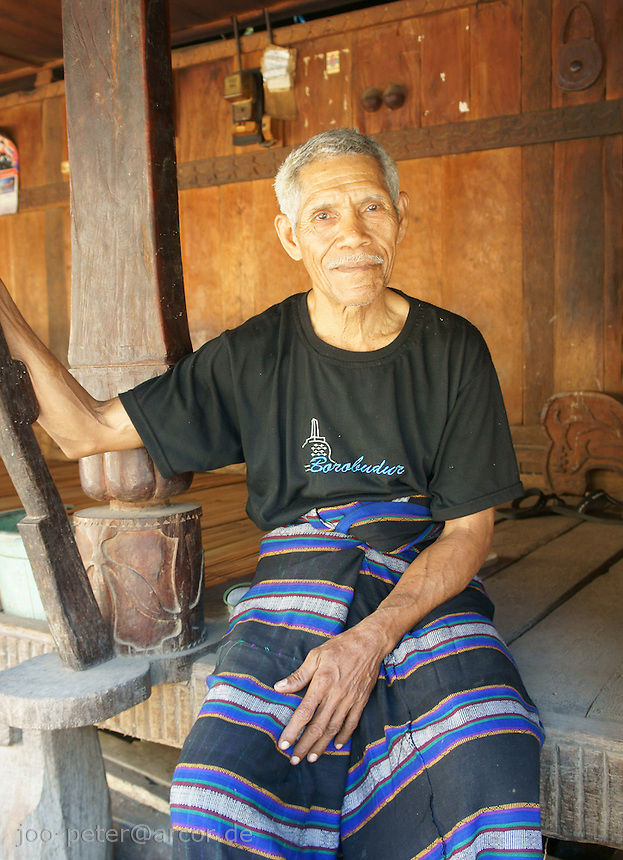 elder villager Bernardus, a very kind and friendly man,  sitting on veranda of his clan  house in fisher village Wolotopo,  island  Flores in archipelago of Indonesia