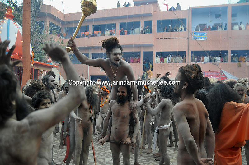 One Naga Sadhu (naked saints) standing on a stick tied around with the penis of another fellow saint during the first Sahi Snan (Royal Bath) at Kumbh Mela  on 12th Feb 2010 . These naga sadhus represent the warrior cult in the Hindu religion and they practice extreme austerity in which they abstain from clothes, relationships and carnal desires. Weathered by such extreme measures they attain prowess that is way beyond a common man's strength. 12th February 2010. Haridwar, Uttarakhand, India, Arindam Mukherjee