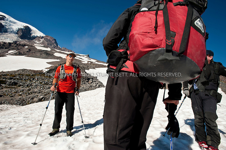 """9/14/2011--Mt. Rainier, WA, USA..Climber Greg Vernovage (foreground), 39, greets Chad Kellogg on his way down Mt. Rainier by saying """"I think we met on Everest""""...Climber Chad Kellogg, 39, training on Mt. Rainier, WASH., for the world speed record climb on Mt. Everest that he will attempt in May, 2012. Kellogg climbs solo and without oxygen...A former competitive luger, Kellogg is a Buddhist who wakes everyday at 4 a.m. to meditate before heading out for training and work. A few years ago, Kellogg had part of his colon removed because of cancer and also lost his first wife to a climbing accident...©2011 Stuart Isett. All rights reserved."""