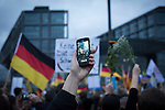 A man filming on a mobile phone as crowds march through the streets of Berlin during a demonstration by the Alternative für Deutschland (AfD) political party. Around 5000 supporters of the AfD took part in the march and rally calling on German Chancellor Angela Merkel to halt the influx of refugees into the country. Around one million refugees from the Middle East and north Africa arrived in Germany during 2015, 50,000 of whom came to Berlin.