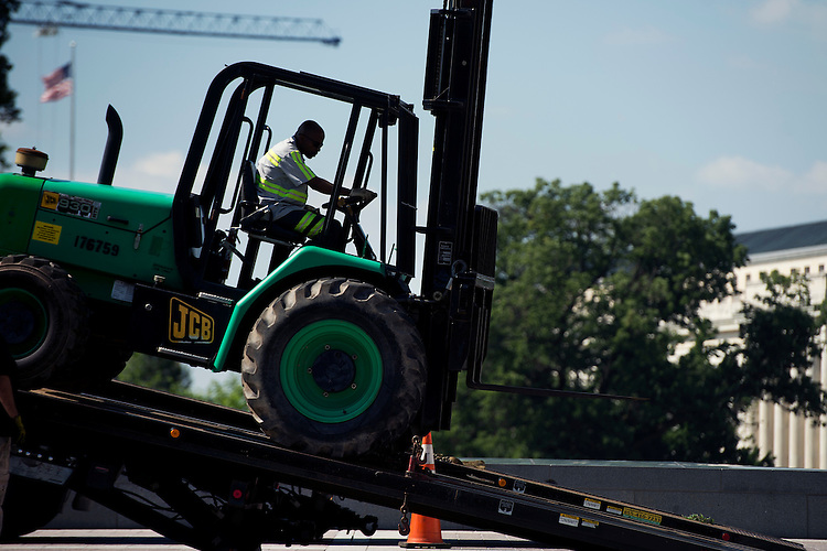 UNITED STATES - JUNE 22: A worker unloads a tractor on the East Front of the Capitol, June 22, 2015. (Photo By Tom Williams/CQ Roll Call)