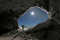 Man stands at the entrance to a glacier ice cave in the Alaska Range mountains, Interior, Alaska.