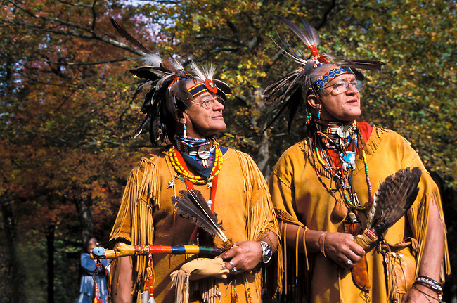 Two traditional Wampanoag men, who are brothers Lee Edmonds and Harry Hawk Edmonds, dressed in buckskin fringed shirts and feather headdresses hold feather dance fans and a dance stick during the annual.Pokanoket/Wampanoag Federation Pow Wow in Slater Park, Pawtucket, RI (MR)