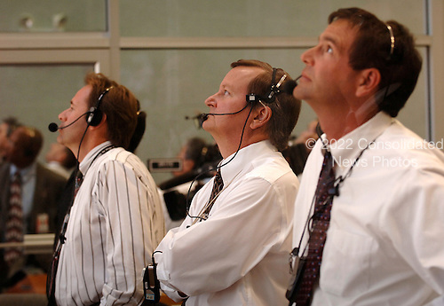 "In Firing Room 4 of the Launch Control Center, Shuttle Launch Director, Mike Leinbach (center) watches the launch of Space Shuttle Discovery on mission STS-121.  Liftoff was on-time at 2:38 p.m. EDT.  During the 12-day mission, the STS-121 crew of seven will test new equipment and procedures to improve shuttle safety, as well as deliver supplies and make repairs to the International Space Station. Landing is scheduled for July 17 at Kennedy's Shuttle Landing Facility. Photo Credit: ""NASA/Bill Ingalls"""