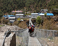 Sherpas carrying their loads across the foot bridge in the village of Phakding on the trail to Lukla, Nepal.
