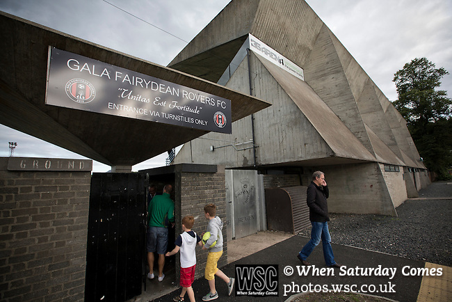 Gala Fairydean Rovers 3 Edinburgh City 3, 13/08/2013. Netherdale, Scottish Lowland Football League. Supporters arriving at the turnstiles prior to watching Gala Fairydean Rovers at their team's first home match in the Scottish Lowland Football League against Edinburgh City at Netherdale in Galashiels. Gala were formed in 2013 by an a re-amalgamation of Gala Fairydean and Gala Rovers, the two clubs having separated in 1908 and their ground in the Scottish Borders had one of only two stands designated as listed football stands in Scotland. The match ended in a 3-3 draw watched by 378 spectators. Photo by Colin McPherson.