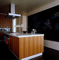 The family-sized modern kitchen has a blackboard running the length of one wall