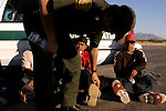 U.S. Border Patrol Agent Robert Marraquin checks the sole tread of illegal aliens, to make sure he's captured the aliens he tracked through the desert near El Centro, Calif. on Wednesday, March 29, 2005. The five aliens walked for about three hours through the desert, making it five miles into the U.S. before being nabbed by the Border Patrol.<br />