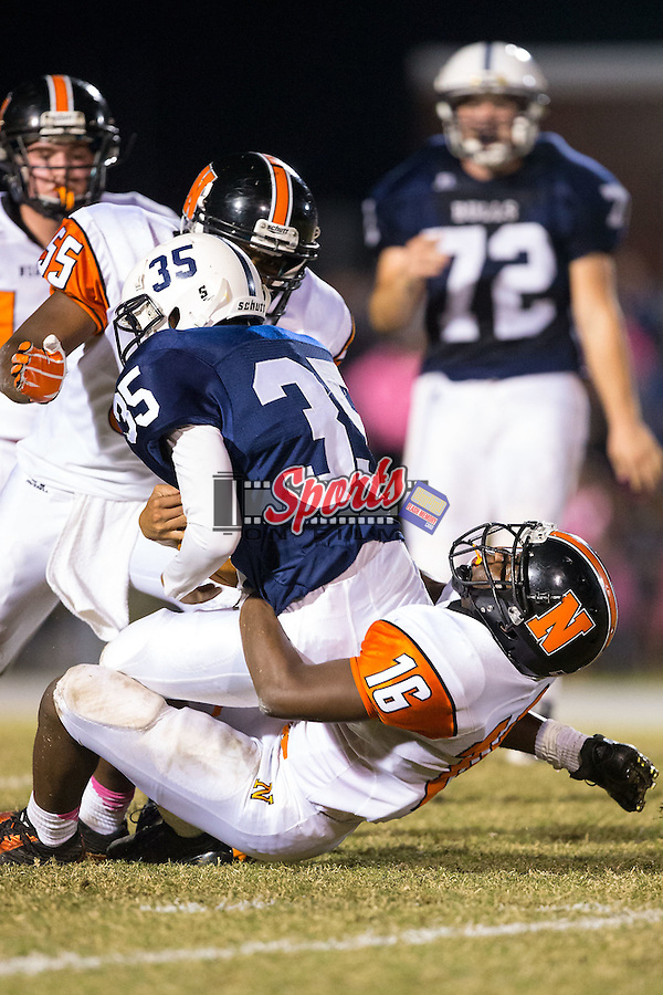 Remington Peters (35) of the Hickory Ridge Ragin' Bulls is tackled from behind by Darian Goolsby (16) of the Northwest Cabarrus Trojans at Hickory Ridge High School on October 17, 2014 in Harrisburg, North Carolina.  The Ragin' Bulls defeated the Trojans 34-6.  (Brian Westerholt/Sports On Film)