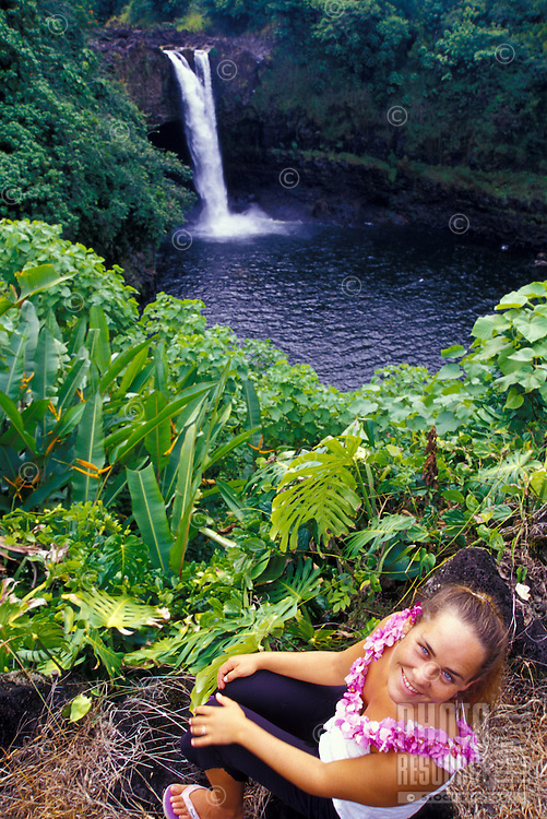 Tourist with orchid lei visits Waianuenue (rainbow) falls in Hilo on the Big Island