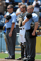 Asheville Tourists catcher Tom Murphy #9 along with first base umpire Cody Oakes and home plate umpire Travis Godec remove there hats for the National Anthem before a game against the Rome Braves at McCormick Field on July 28, 2013 in Asheville, North Carolina. The Braves won the game 9-3. (Tony Farlow/Four Seam Images)