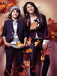Smiling boy and a teenage girl in fashionable clothes and red falling autumn leaves beautiful artistic fall fashion photo