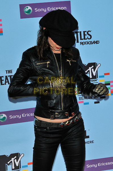 JULIETTE LEWIS .during the MTV Europe Music Awards 2009 at the O2 World Arena in Berlin, Germany, November 5th 2009..arrivals EMA EMAs half length cap hat black leather jacket unzipping gold gloves  studded studs belt head down undoing .CAP/PL.©Phil Loftus/Capital Pictures