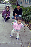 Berkeley CA Adoptive parents (Dad Cuban) of Guatemalan baby, eleven-months-old, proudly observing her new walking skills, MR