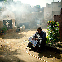 Egypt / Cairo / 10.3.2012 / A man reads the newspaper in St George Cemetery in Old Cairo (Coptic Cairo). Egypt, March 2012.