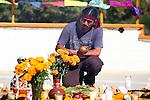 Indigenous man kneels before floral arrangement in honor of deceased family members. Tecate, Baja California. Mexico.<br /> (4)