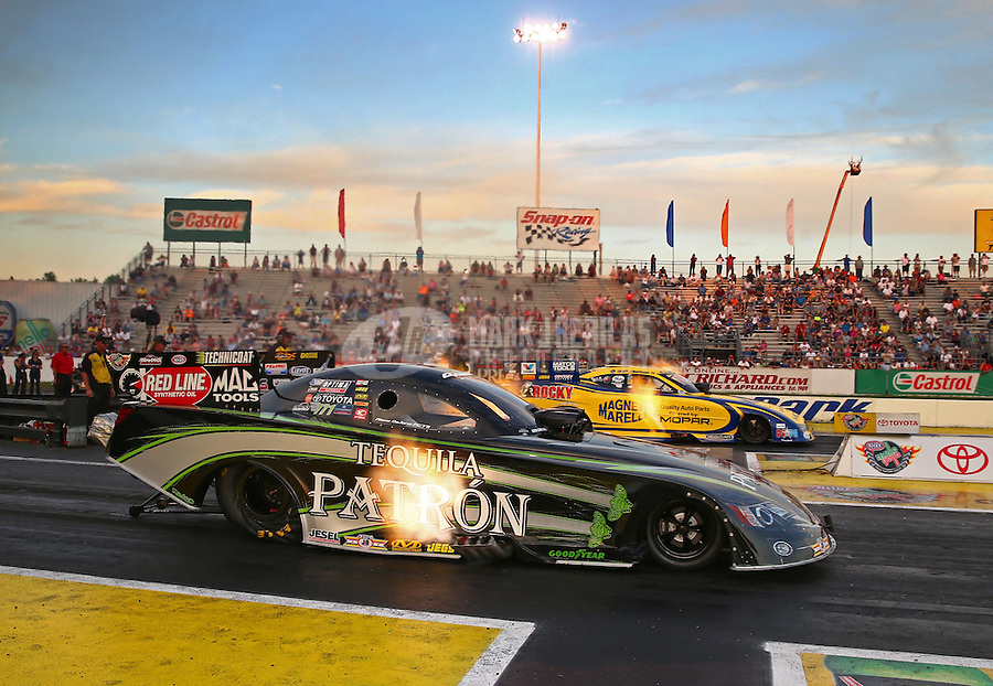 May 31, 2013; Englishtown, NJ, USA: NHRA funny car driver Alexis DeJoria (near) races alongside Matt Hagan during qualifying for the Summer Nationals at Raceway Park. Mandatory Credit: Mark J. Rebilas-