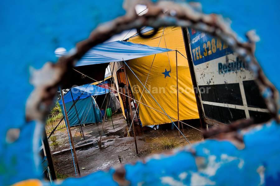 A view through a ticket office showing temporary tents at the Circo Anny, a family run circus wandering the Amazon region of Ecuador, 4 July 2010. The Circo Anny circus belongs to the old-fashioned traveling circuses with a usual mixture of acrobat, clown and comic acts. Due to the general loss of popularity caused by modern forms of entertainment such as movies, TV shows or internet, these small family enterprises balance on the edge of survival. Circuses were pushed away and now they have to set up their shows in more remote villages. The circus art and culture is slowly dying.