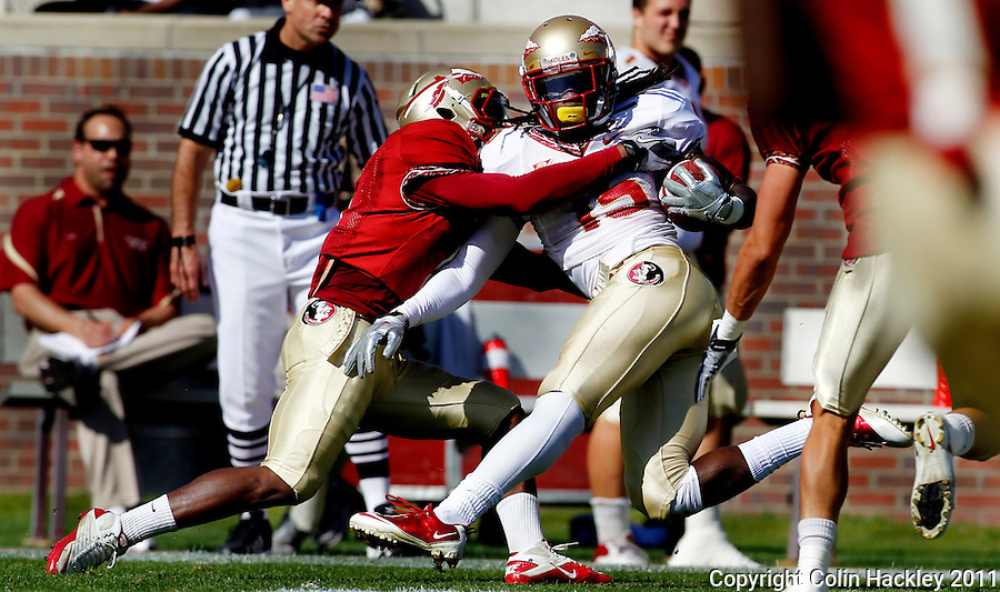 TALLAHASSEE, FLA. 4/16/11-FSUG&G041611 CH-Garnet's Greg Reid tackles Gold's Greg Dent during first half action in the Florida State University Garnet and Gold game Saturday in Tallahassee..COLIN HACKLEY PHOTO