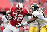 November 14, 2009: Wisconsin Badgers running back John Clay (32) stiff arms Michigan Wolverines defensive back Donovan Warren (6) during an NCAA football game at Camp Randall Stadium on November 14, 2009 in Madison, Wisconsin. The Badgers won 45-24. (Photo by David Stluka)