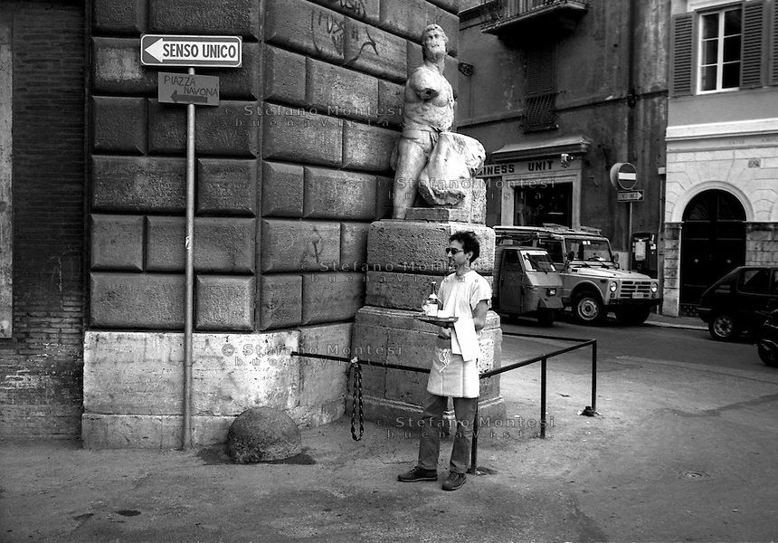 Roma  1996.Cameriere passa davanti alla statua di Pasquino,la più celebre statua parlante di Roma..Rome 1996.Waiter it passes in front of the statue of Pasquino,la more famous speaking statue in Rome.He finds' corner of Piazza di Pasquino and Palazzo Braschi, on the west side of Piazza Navona .http://en.wikipedia.org/wiki/Pasquin..