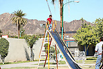 Father diligently watches his small child happily ride down the slide.<br /> (2)