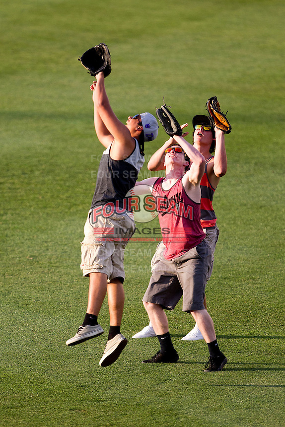 Three fans battle for a ball in a fly ball contests for a free pizza during a game between the Arkansas Travelers and the Springfield Cardinals at Hammons Field on June 13, 2012 in Springfield, Missouri. (David Welker/Four Seam Images)
