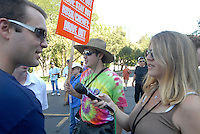 24 Aug 08: An individual talks to a reporter prior to the start of a march from the steps of the Colorado state capitol building to the Pepsi Center. On the day before the Democratic National Convention is scheduled to begin about 1,500 people participated in the ReCreate 68 rally, which included a march from the Colorado state capitol building to the Pepsi Center.
