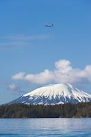 Alaska airlines jet flies over the top of Mount Edgecumbe, near Sitka, southeast Alaska.