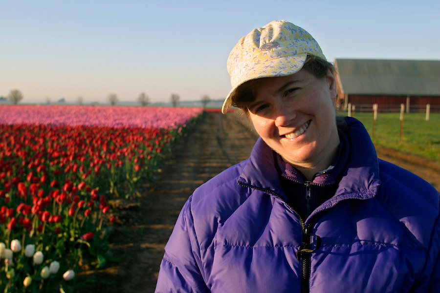 Woman smiling in field of pink and red tulips, Mount Vernon, Skagit Valley, Skagit County, Washington, USA