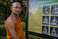 Borobudur, Java, Indonesia.  Young Buddhist Monk Reading about the Buddha Statues on the Temple.