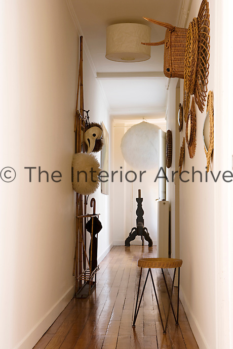 The narrow corridor is furnished with an eclectic collection of objects