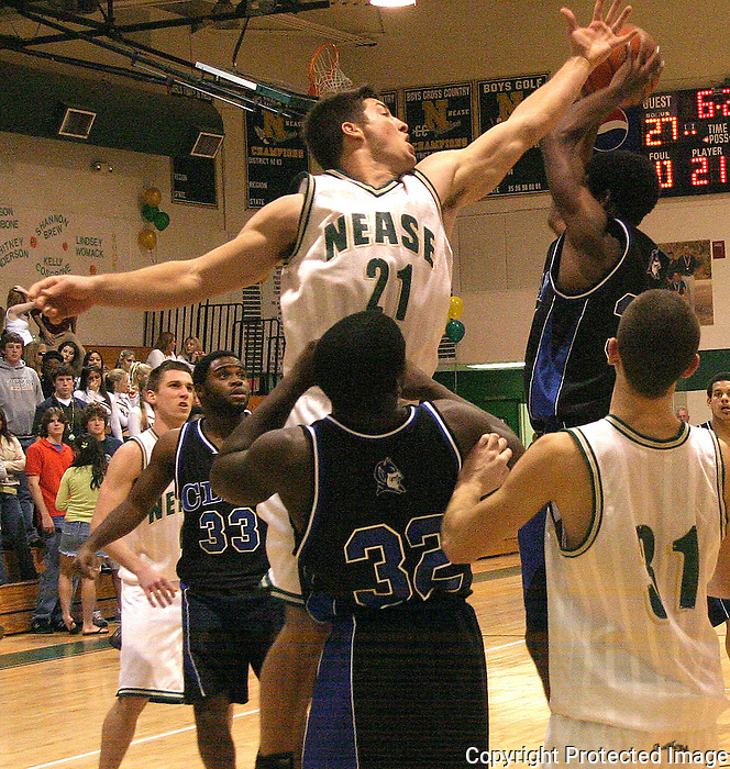 02/11/05.....Gary Wilcox/staff...Nease Boys Basketball Player Tim Tebow (21)  blocks  Clay High School Basketball player Winick Cine (34) at the St. Johns River Conference play-offs at Nease High last Friday (02/11/05. Nease won 57 to 53.