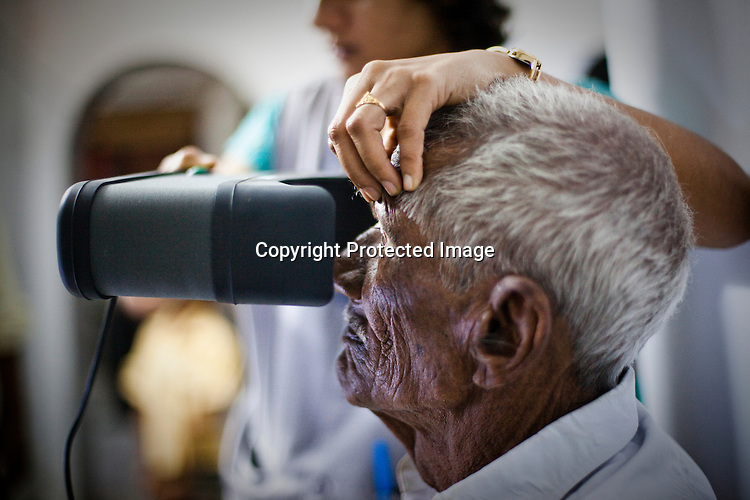 An official holds up the eyebrows for 95 year old Gandaiah during the  iris scanning process as part of the  enrollment process in Naagaaram village, outskirts of Hyderabad in Andhra Pradesh, India. India is assigning each one of its 1.2 billion people a unique ID number based on digital finger prints and iris scan. Photograph: Sanjit Das/Panos