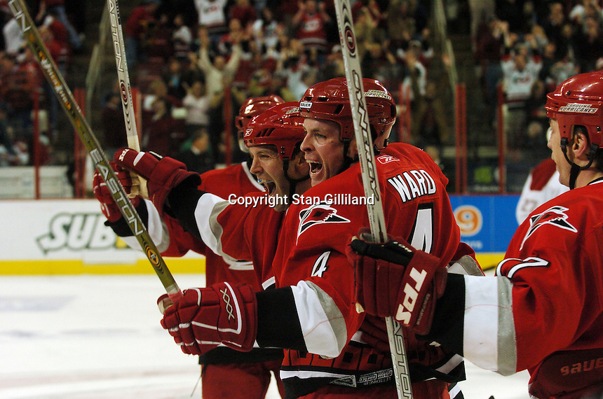 Carolina Hurricanes' defenseman Aaron Ward (4) celebrates his last second goal against the Montreal Canadiens with teammate Bret Hedican, left, and Rod Brind'Amour, right, Saturday, Dec. 31, 2005 in Raleigh, NC. Carolina won 5-3.