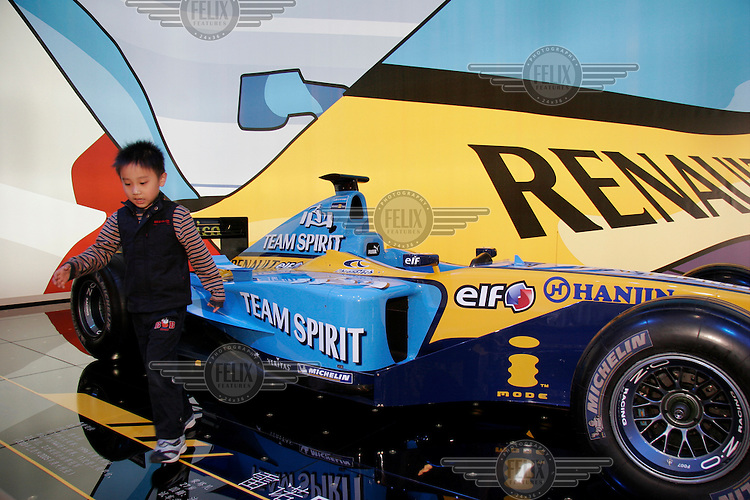 A child plays beside a Renault Formula One (F1) race car on display at the Auto Shanghai 2005 exposition. With global car manufacturers increasingly interested in the potential of the Chinese market, the exhibition has become one of the largest of its kind in Asia.