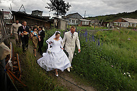 Bride Miroslava Osipova and her new husband Ivan Osipova are followed by family as they walk through the neighborhood.  She is seven months pregnant. Weddings are huge events in small communitites in remote regions of Kamchatka.<br /> ALL ARE RELEASED.