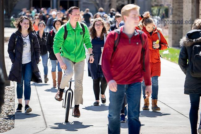 April 19, 2018; Ryan Mas rides a unicycle to class. (Photo by Matt Cashore/University of Notre Dame)