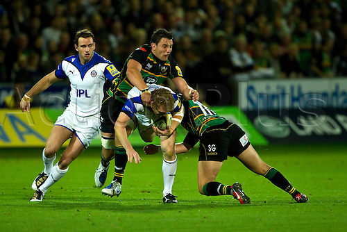 Bath's Sam Vesty (white) is tackled by Northampton's Phil Dowson and Sean Geraghty (green) during their teams' Aviva Premiership match at Franklin's Gardens on 17th September 2010.  Northampton won the match 31-10.