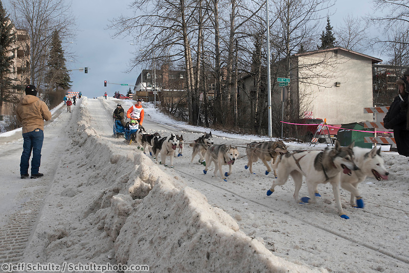 Jr Champion and team run past spectators on the bike/ski trail with an Iditarider in the basket during the Anchorage, Alaska ceremonial start on Saturday, March 5, 2016 Iditarod Race. Photo by O'Hara Shipe/SchultzPhoto.com